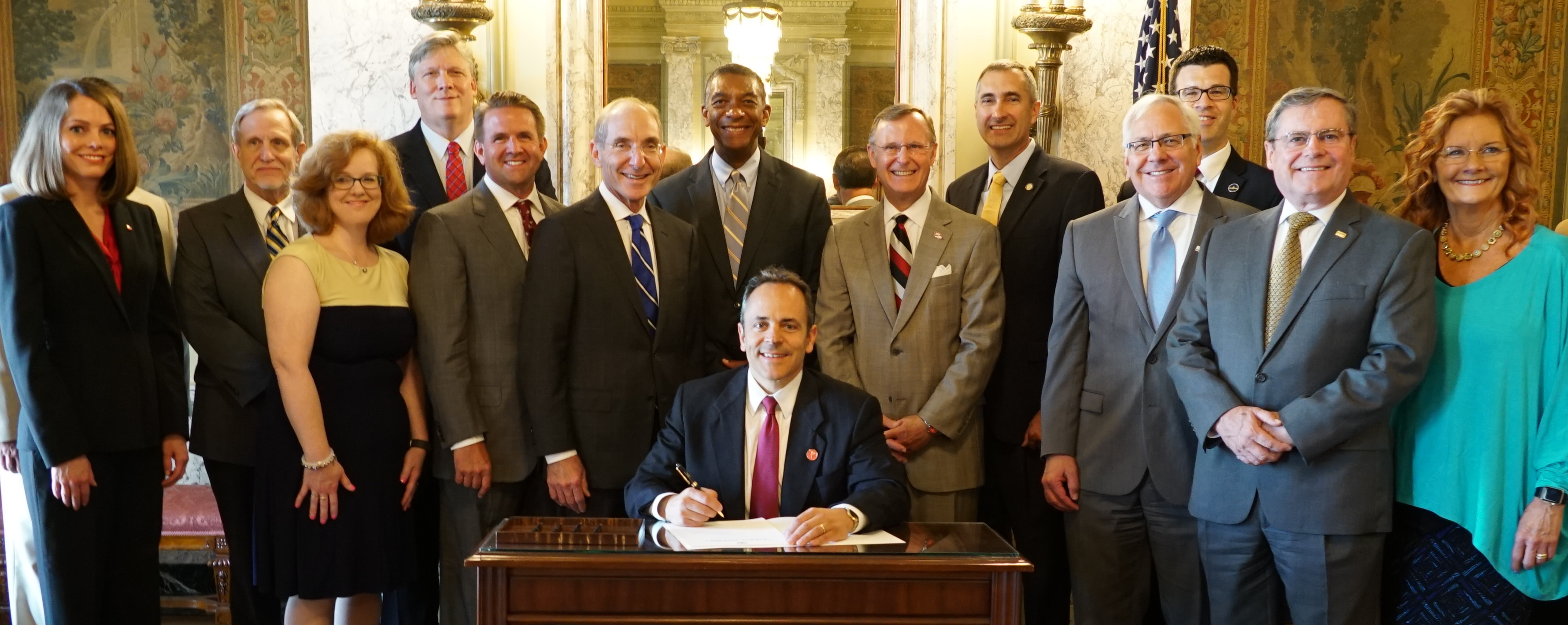 Gov. Matt Bevin ceremonially signs SB 153, the new performance funding bill while campus presidents and representatives look on.